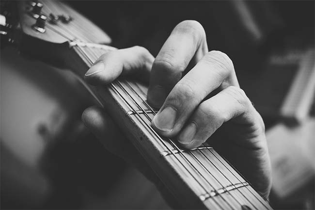 Man Playing Guitar Chord: Black and White